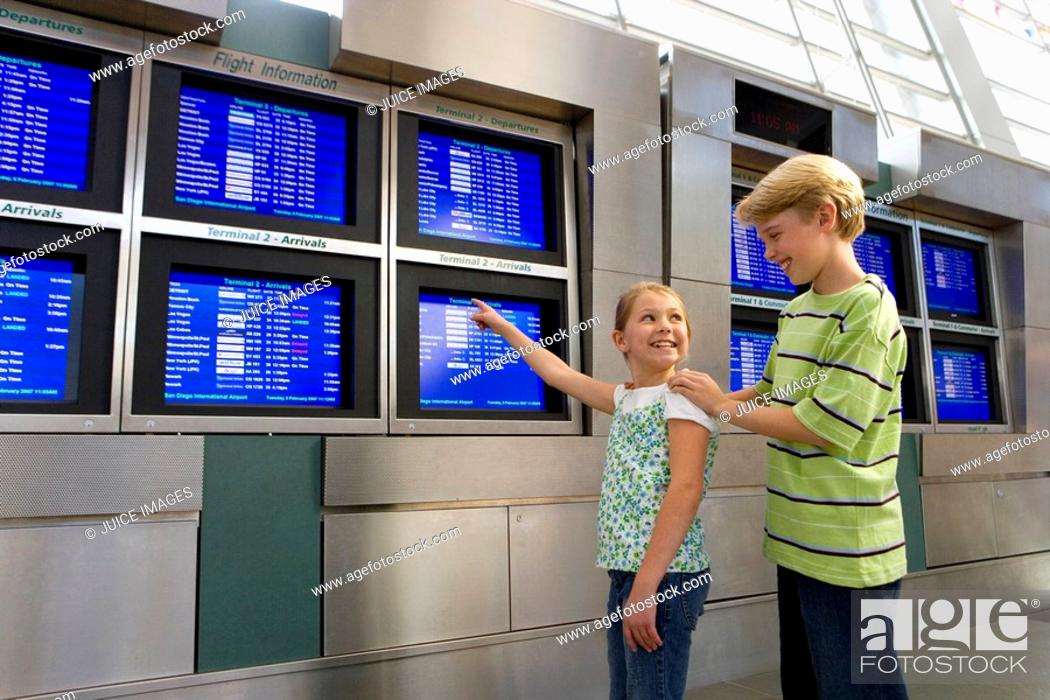 Stock Photo: Brother 8-10 and sister 7-9 looking at flight information screen in airport departure lounge, girl pointing, smiling.
