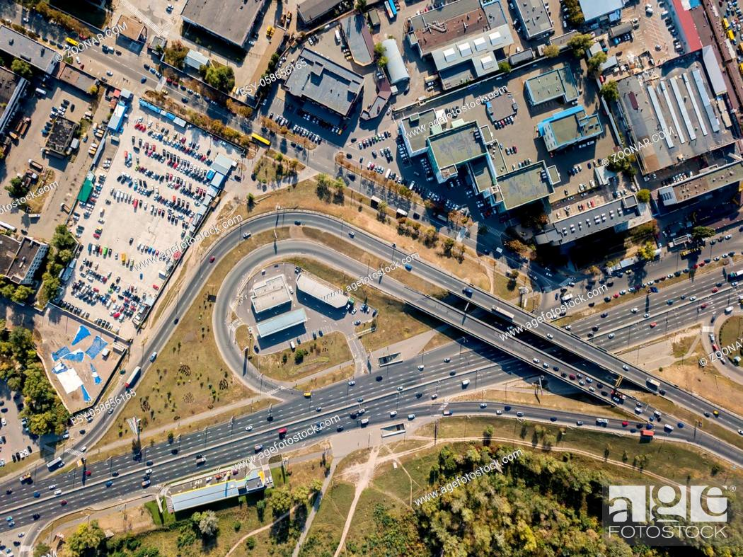 Imagen: Roadway with bridge in Kyiv. There is a park, car parking and buldings around it. Top view panoramic photo. Horizontal.