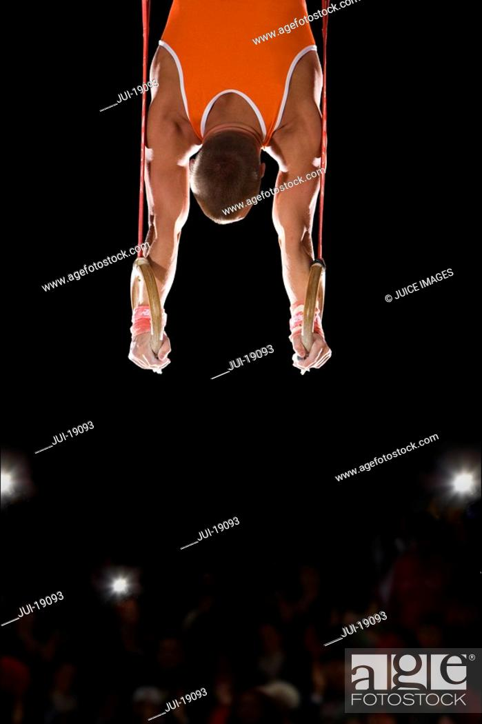 Stock Photo: Male gymnast performing on gymnastic rings, rear view.