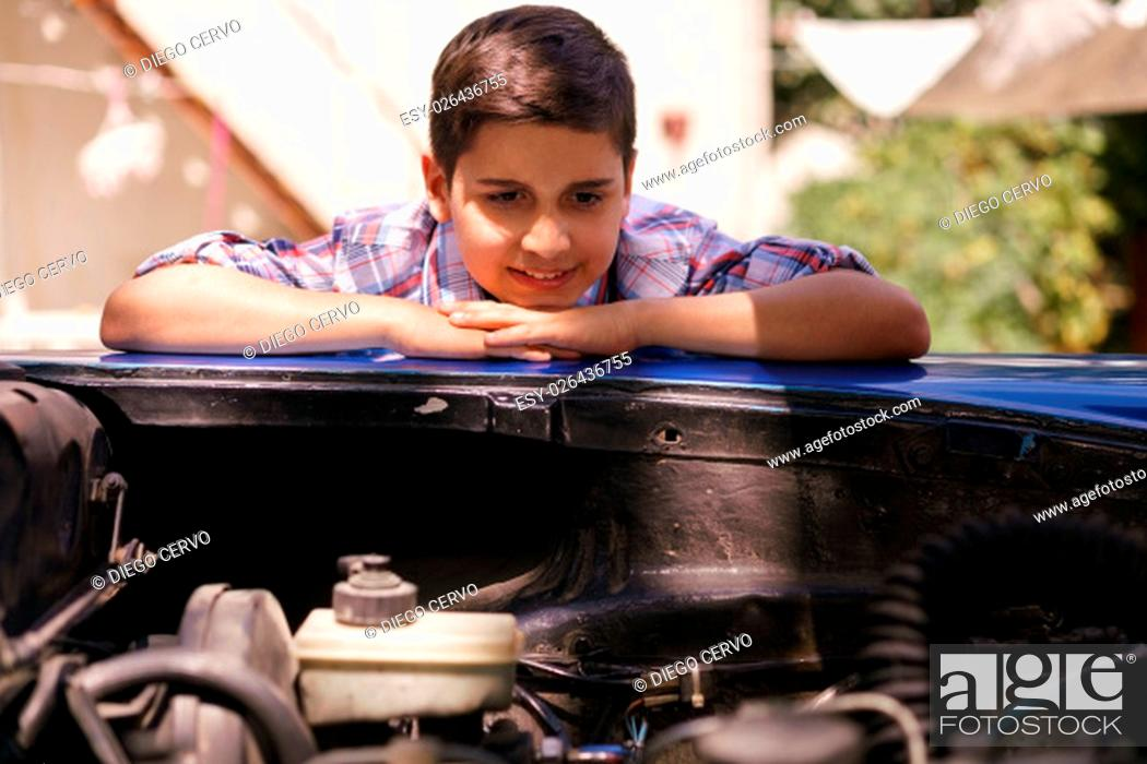 Stock Photo: Preteen child looking at the engine of a vintage car from the 60s. He is amazed and excited. The boy smiles happy and leans against the open hood with chin on.