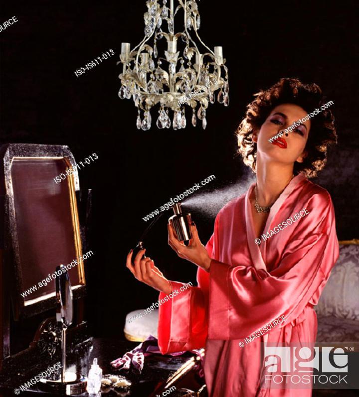 Stock Photo: Young woman spraying perfume.