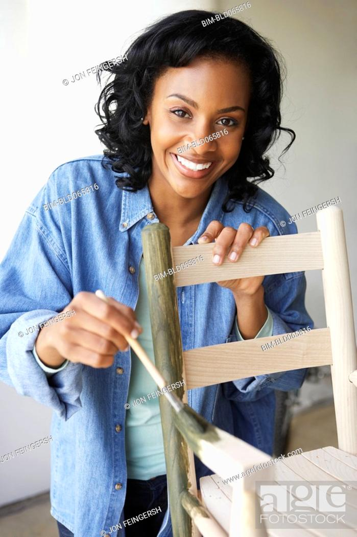 Stock Photo: African woman painting rocking chair.