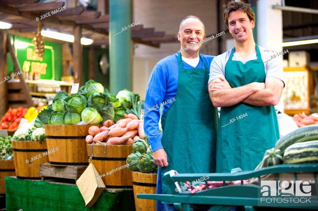 Stock Photo: Green grocers by shop, smiling, portrait.