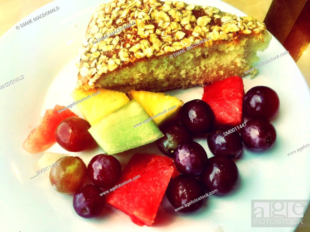 Imagen: Slice of cake and fresh fruit pieces on plate.
