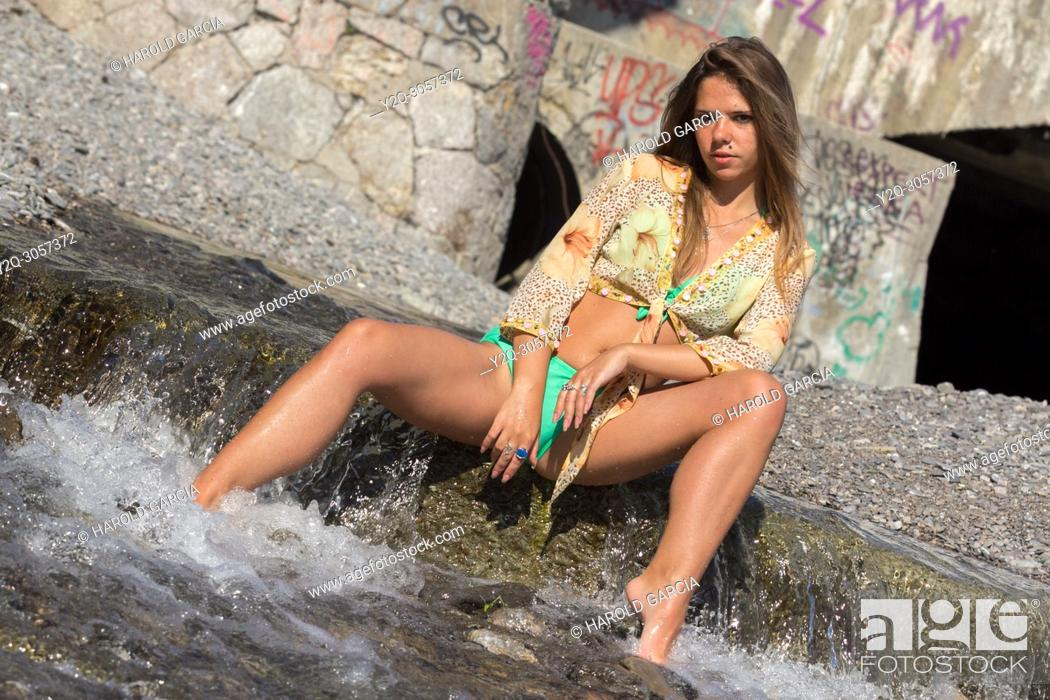 Imagen: Sexy woman with a beautiful body wetting the feet on the river water's and posing sensually in Yalta, Crimea.