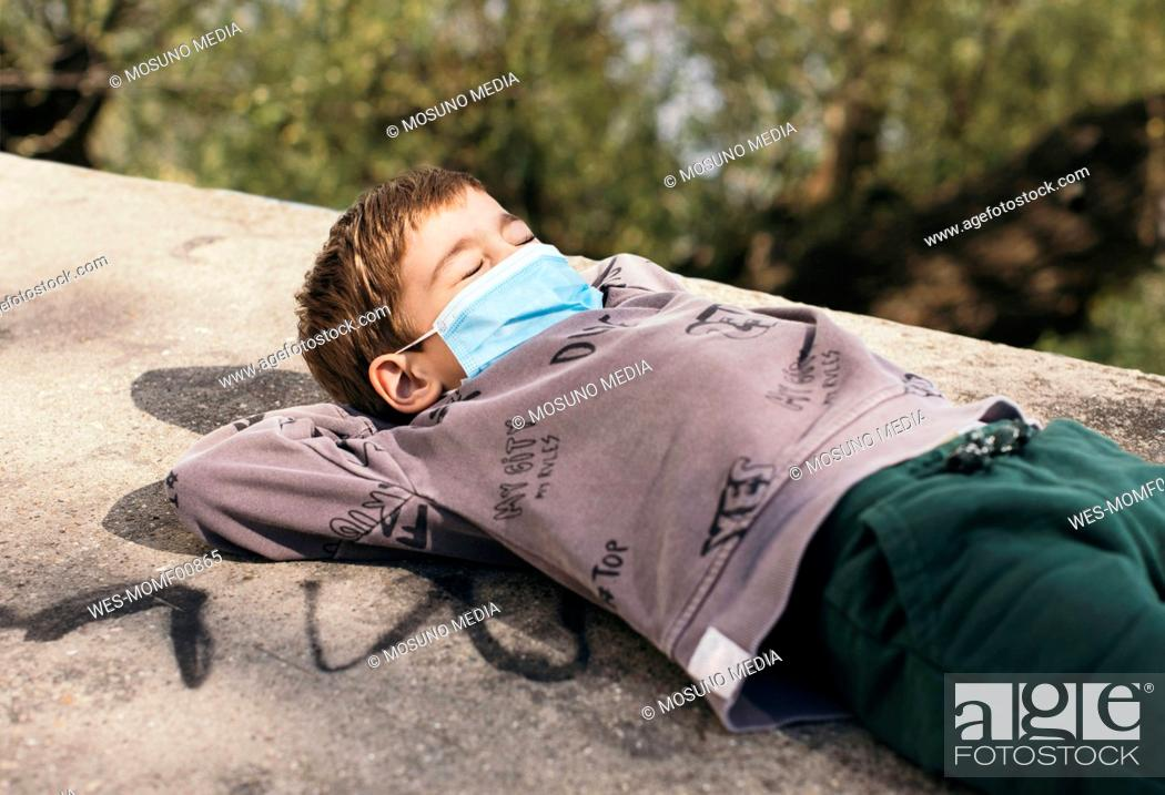 Stock Photo: Portrait of boy with eyes closed wearing protective relaxing on a wall.