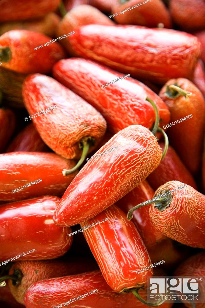 Stock Photo: Pile of red Serrano peppers at produce market.