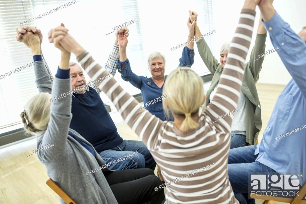 Stock Photo: Group of seniors practicing chair gymnastics with instructor in retirement home.
