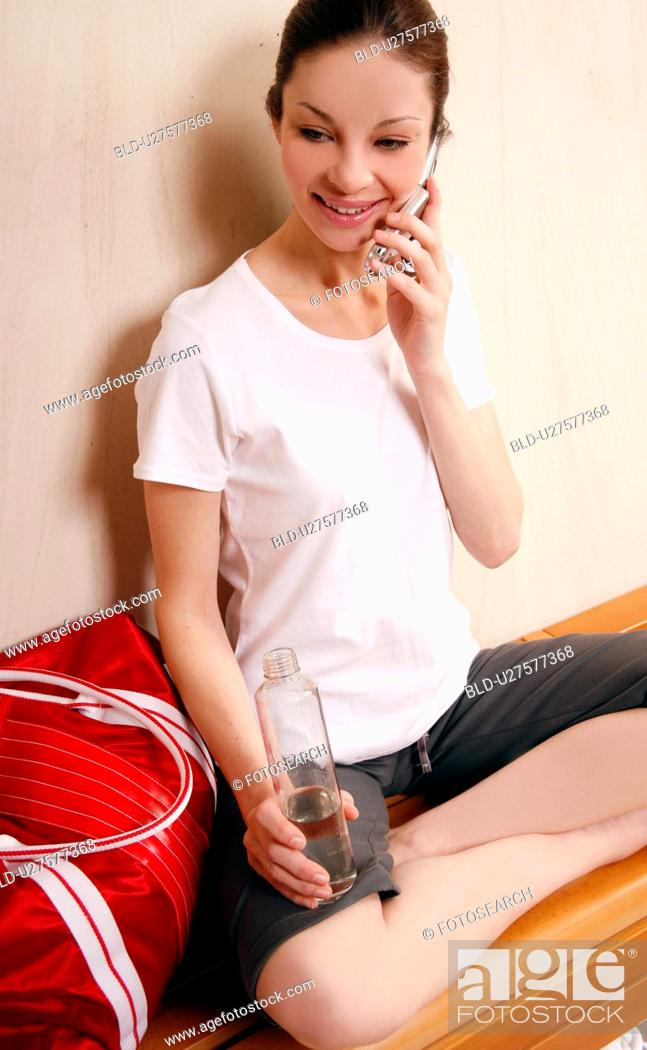 Stock Photo: Woman relaxing in locker room after the gym.