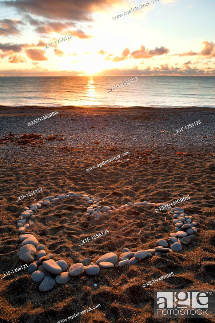 Stock Photo: A heart shape made from pebbles at sunset on Aberystwyth beach wales UK.