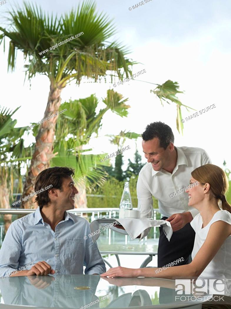 Stock Photo: Waiter serving a couple.