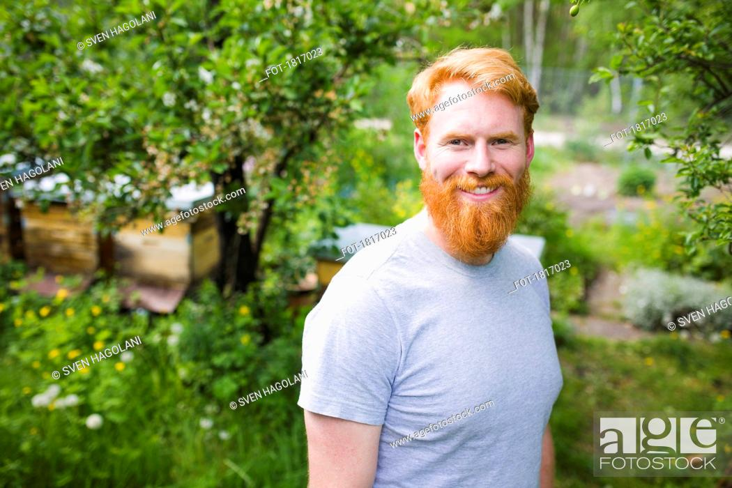 Stock Photo: Portrait smiling, confident man with red hair in garden.
