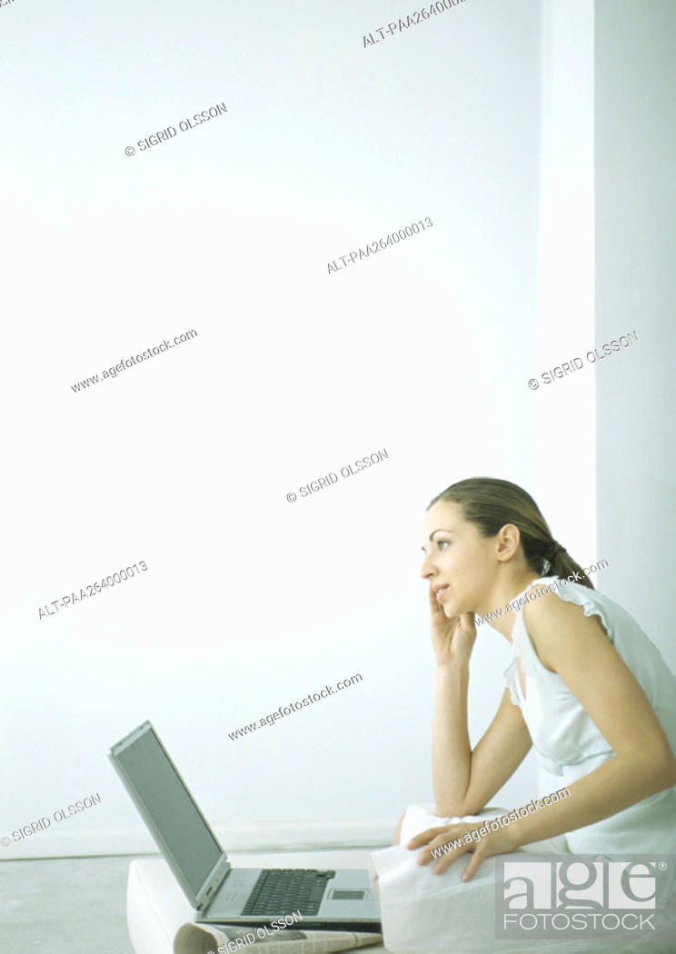 Stock Photo: Young woman sitting on floor with laptop, holding cell phone to ear.