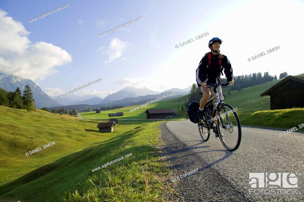 Stock Photo: Germany, Bavaria, Mittenwald, Woman mountain biking across highway.