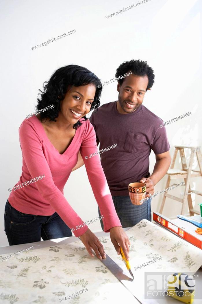 Stock Photo: African couple measuring wallpaper.