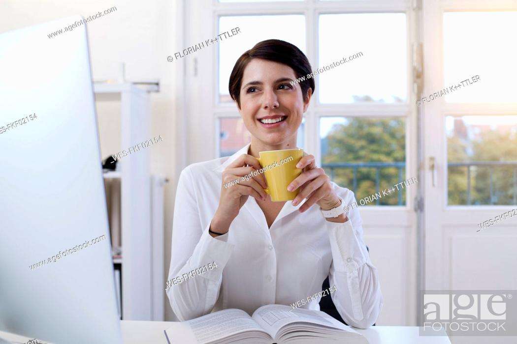 Stock Photo: Smiling woman holding cup of coffee at desk in office.