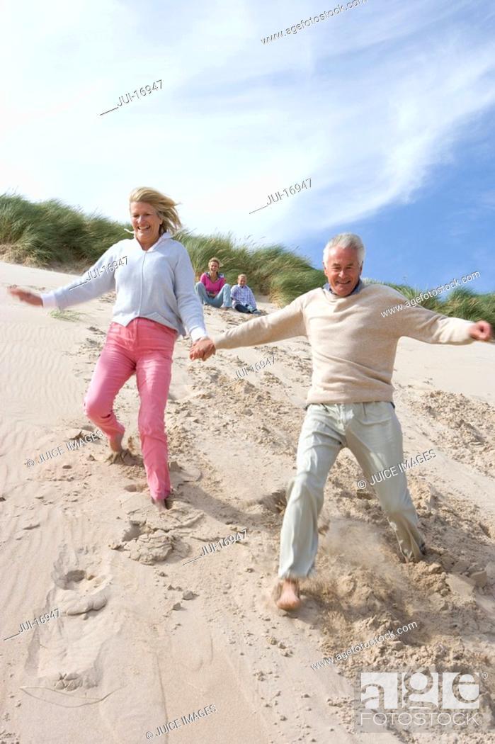 Stock Photo: Senior couple running down on beach.