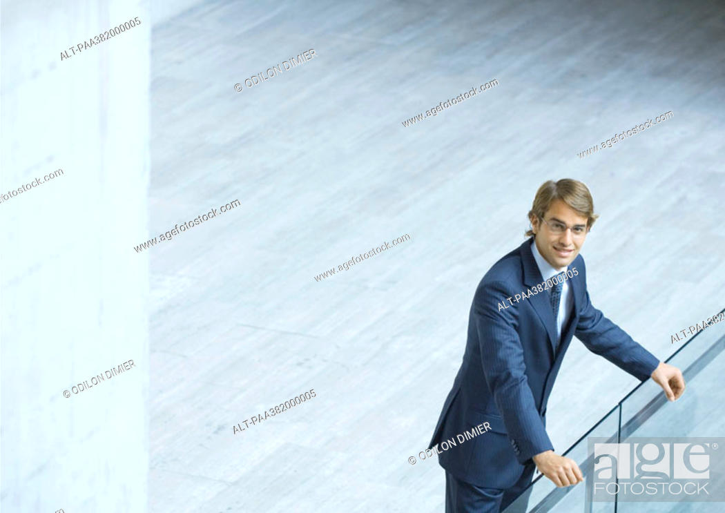 Stock Photo: Businessman leaning on railing, high angle view.