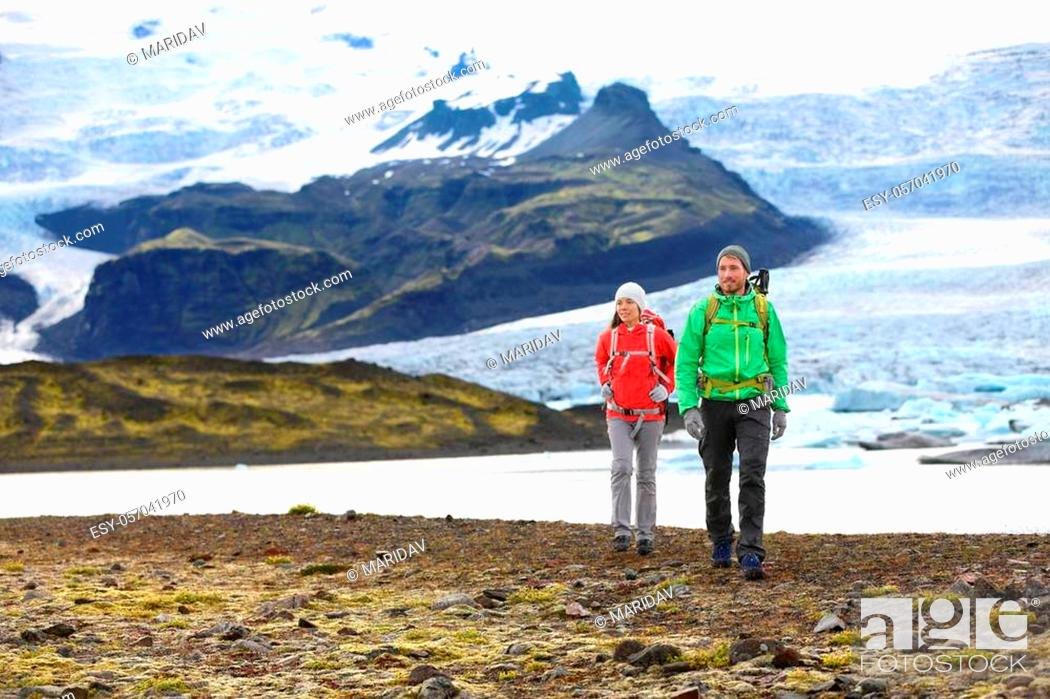 Stock Photo: Adventure hiking travel couple trekking on Iceland. People by glacier and glacial lagoon / lake of Fjallsarlon, Vatna glacier, Vatnajokull National Park.
