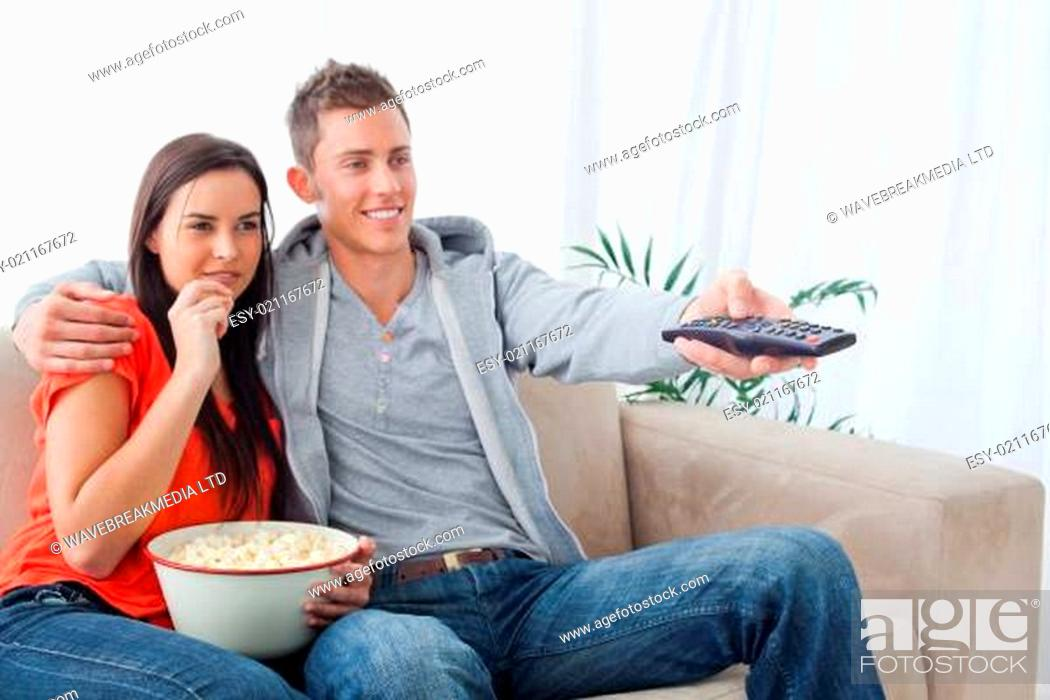 Stock Photo: A side view shot of a smiling couple enjoying a tv show while having popcorn.