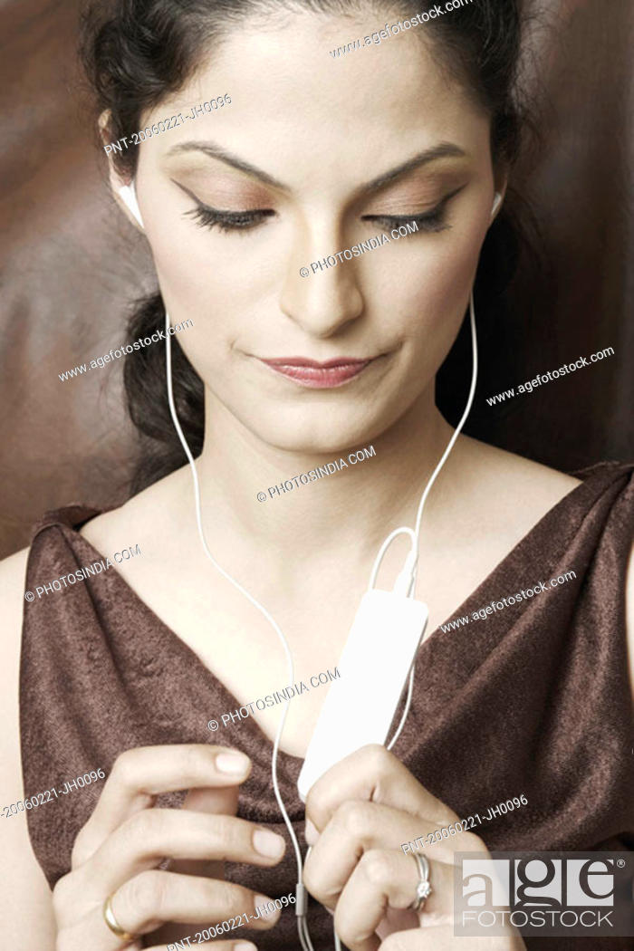 Stock Photo: Close-up of a young woman listening to an MP3 player.