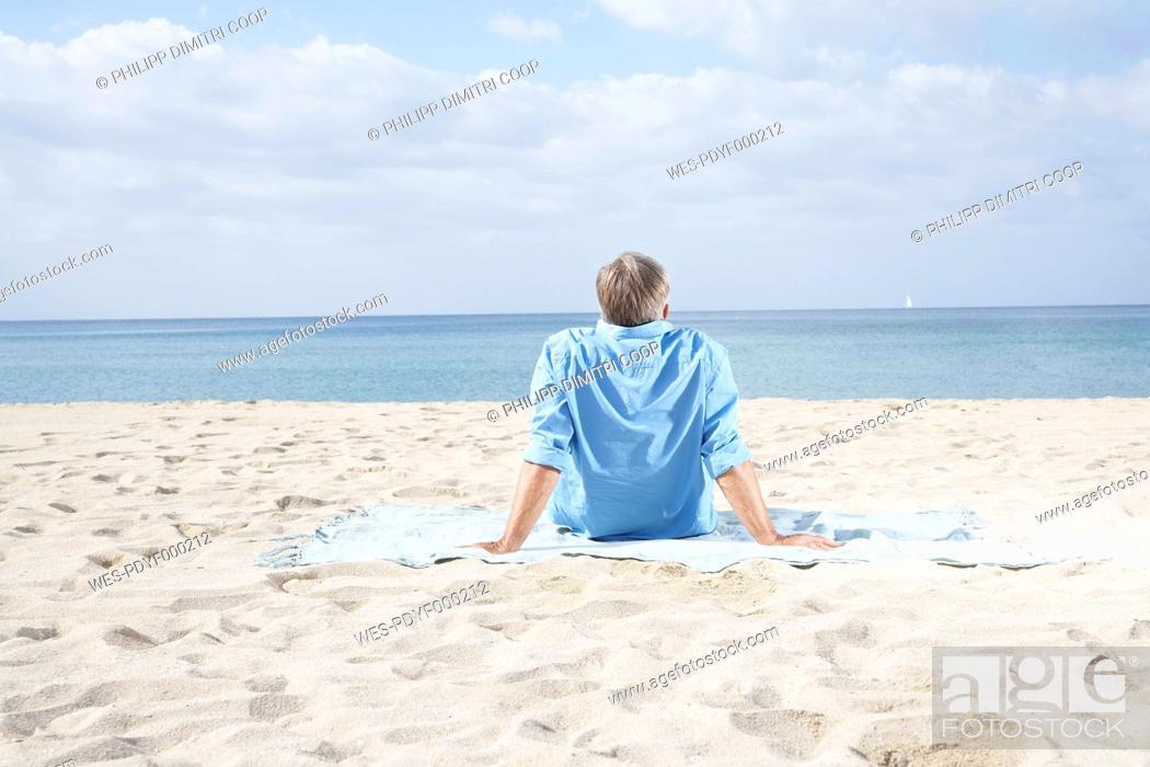 Stock Photo: Spain, Senior man sitting on beach.