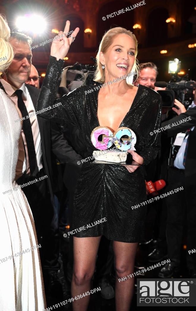 Stock Photo: 07 November 2019, Berlin: US actress Sharon Stone makes a Vicory Mark while holding the Woman of the Year Award in her hand at the 2019 GQ Men of the Year.