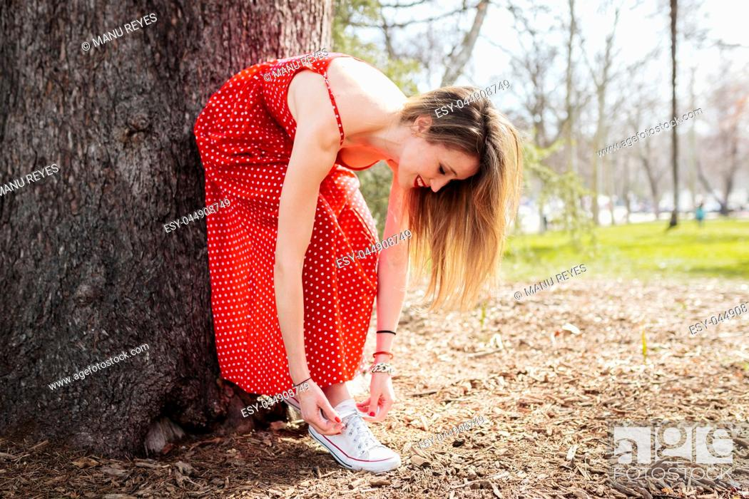 Stock Photo: Young smiling blond woman leaning tying her sneakers whit dress.