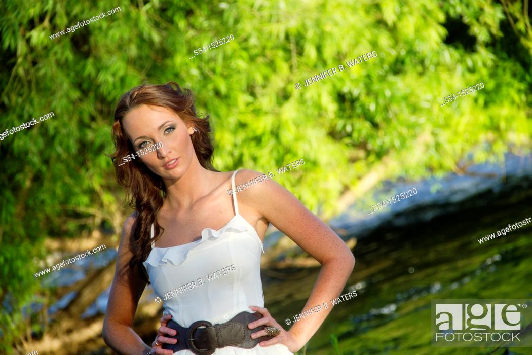 Stock Photo: A beautiful young caucasian woman outdoors in Spokane, Washington, USA, standing in the Spokane River.