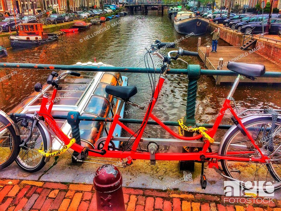Imagen: Tandem bicycle chained to railings above canal, Amsterdam, Netherlands.