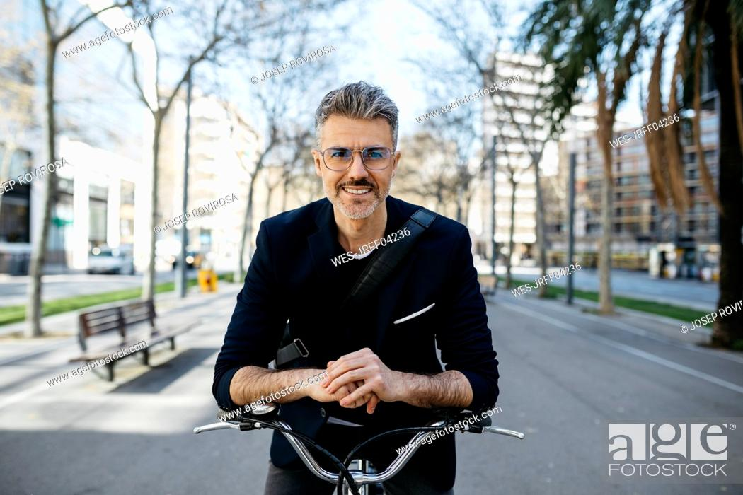 Stock Photo: Portrait of a gray-haired businessman with bicycle in the city.