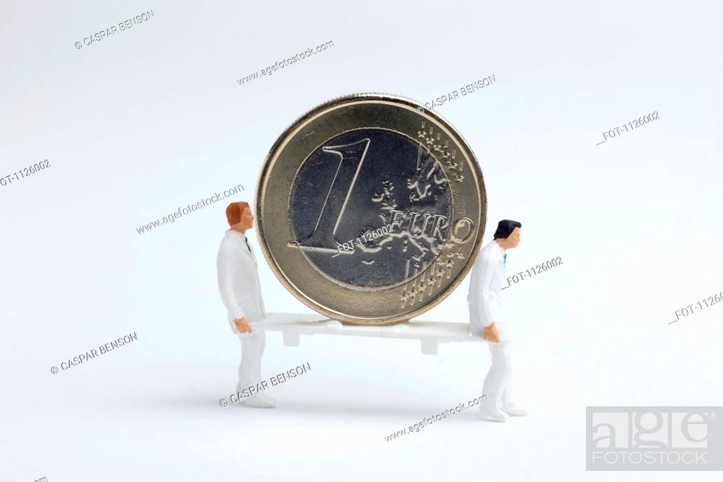 Stock Photo: Miniature paramedic figurines carrying a euro coin on a stretcher.