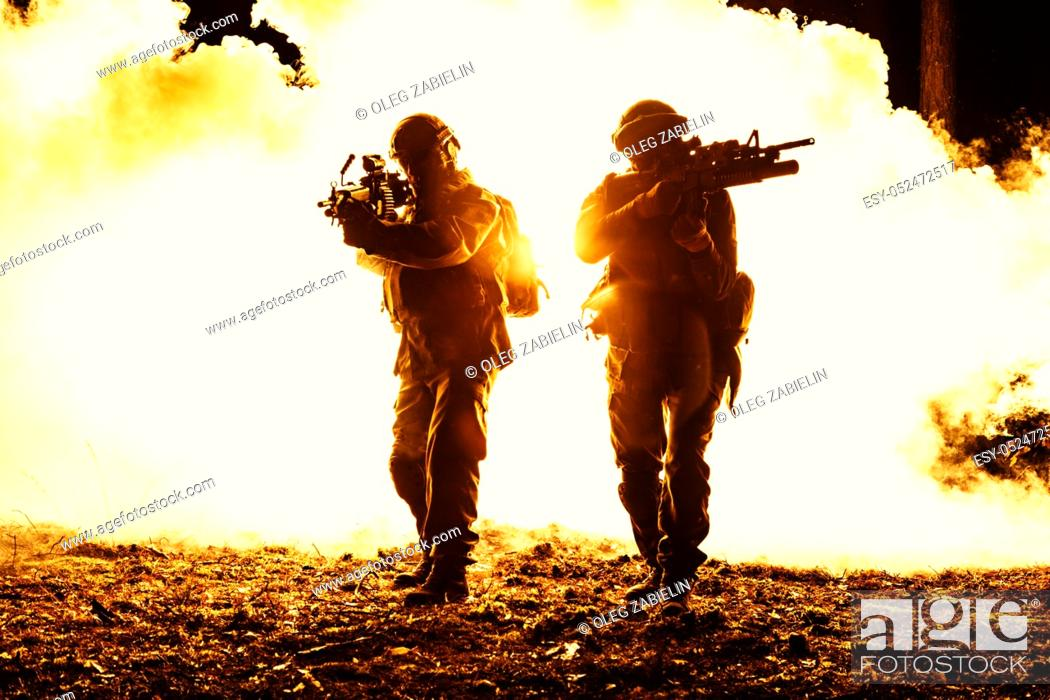 Imagen: Black silhouettes of pair of soldiers in the smoke fire burning moving in battle operation. Back light.