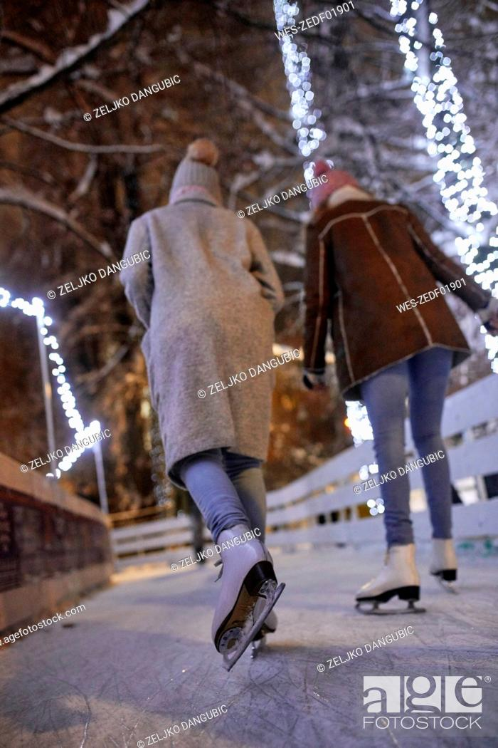 Stock Photo: Rear view of friends ice skating on an ice rink at night.