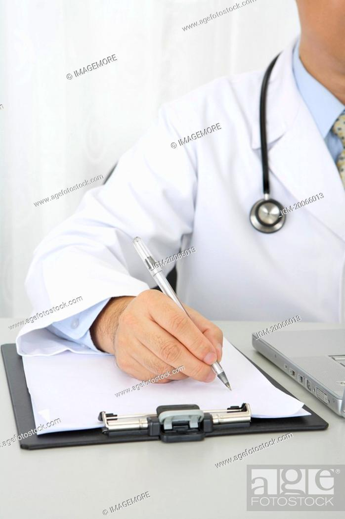 Stock Photo: Doctor writing on the clipboard.