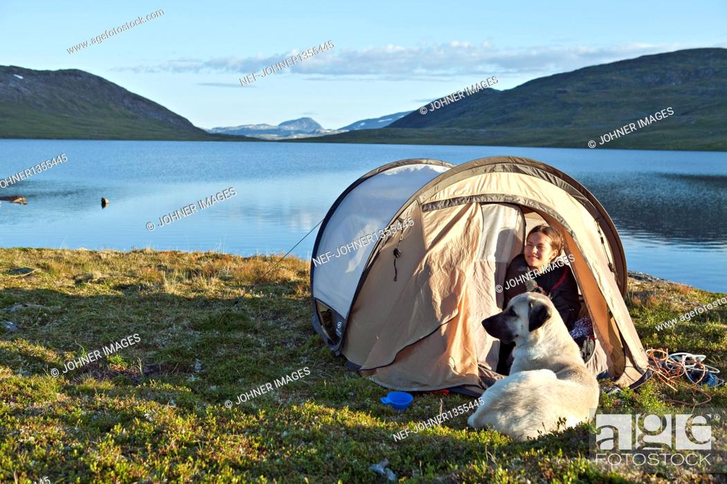 Stock Photo: Tourist with dog in tent on lakeshore.