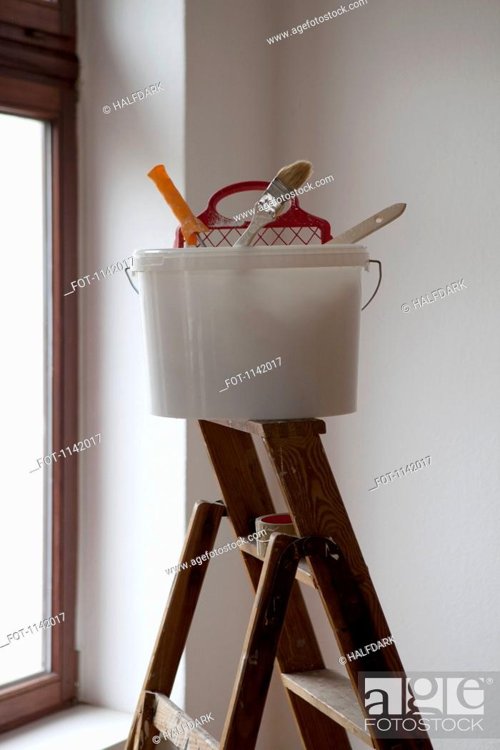 Stock Photo: A bucket of painting equipment on a ladder.