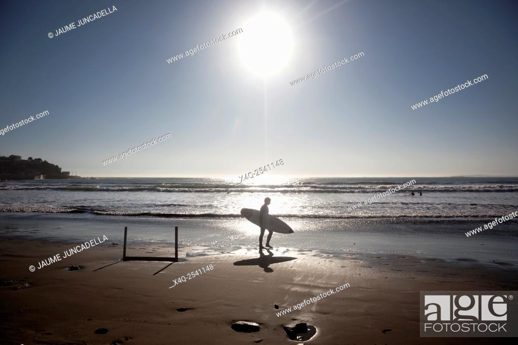 Stock Photo: Surfer walks along the beach after a fun time in the water. Image is backlit and features the subject in silhouette.
