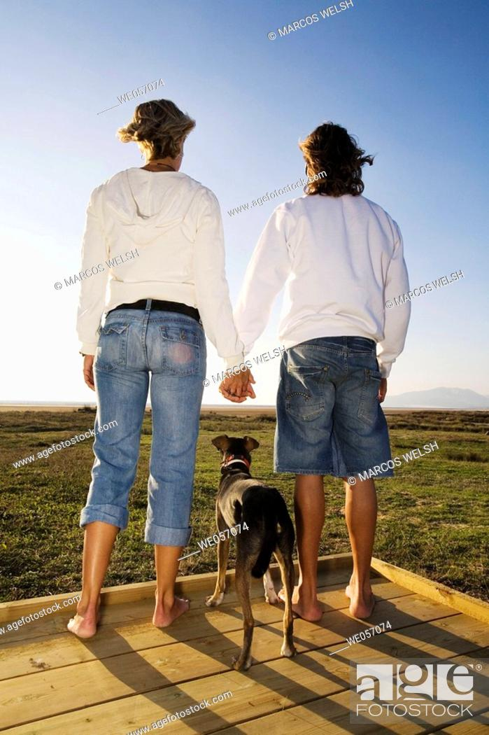 Stock Photo: Couple With Their Dog Enjoying Scenery.