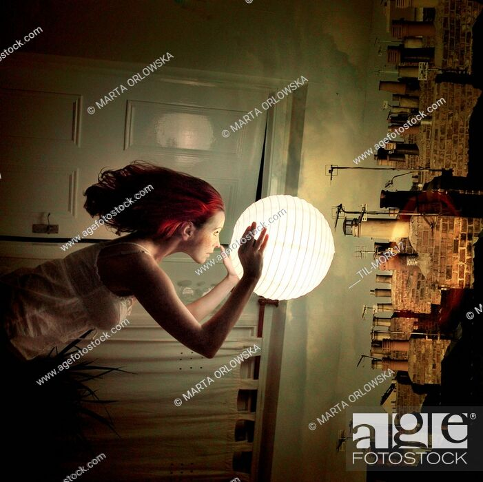 Imagen: Conceptual image of young woman holding a paper lamp over chimney stacks.