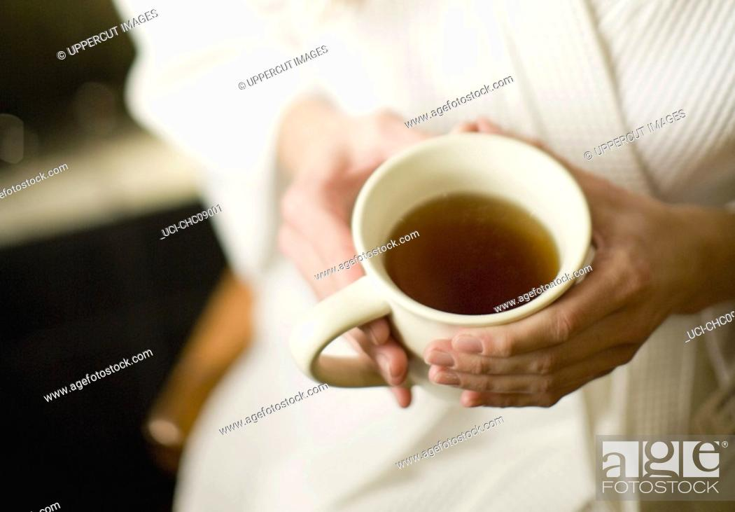 Stock Photo: Woman holding cup of tea.