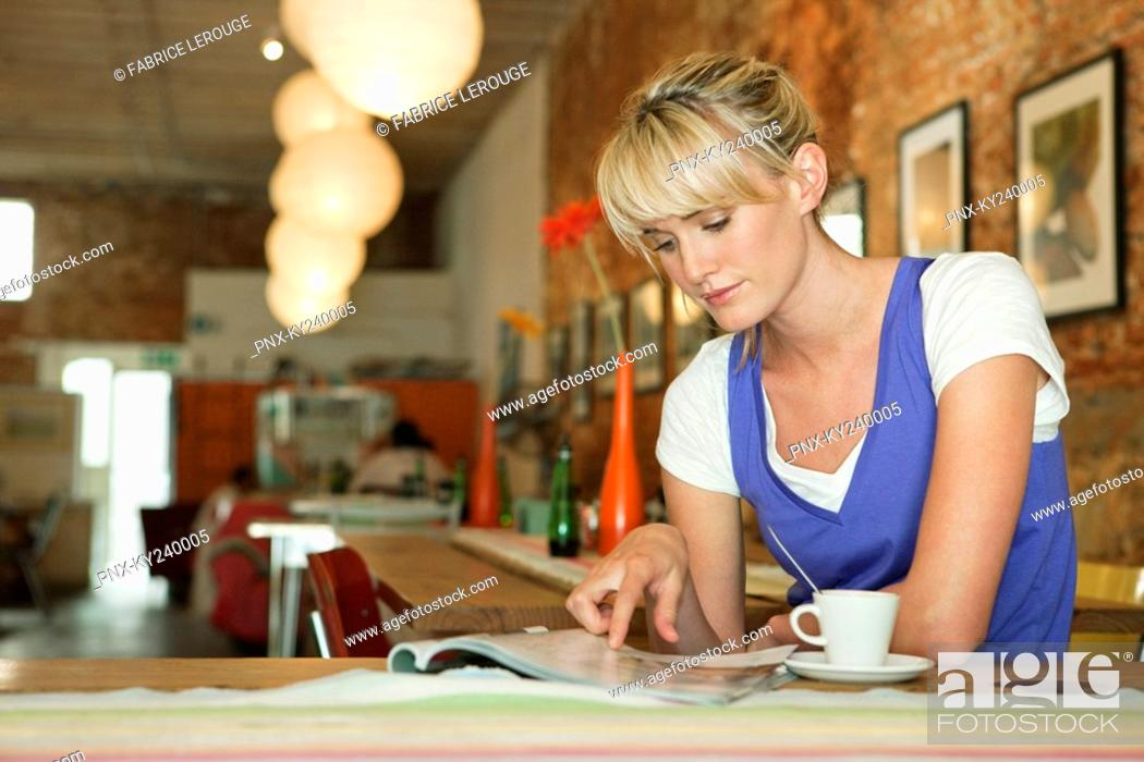 Stock Photo: Woman reading a magazine in a cafe.