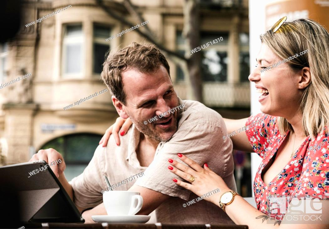 Stock Photo: Happy couple with tablet at an outdoor cafe.