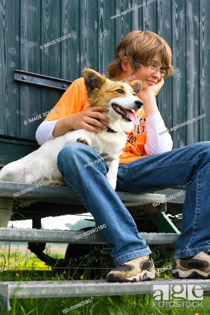 Stock Photo: Boy sitting on a step with his dog.