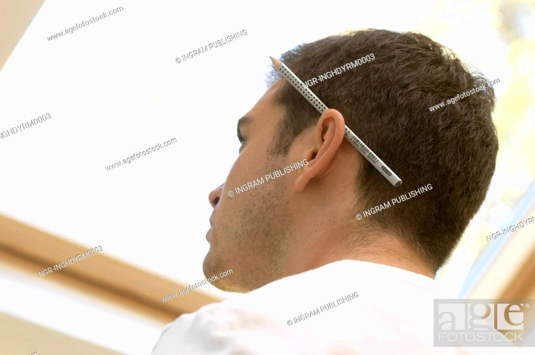 Stock Photo: Close-up of a young man with a pencil behind his ear.