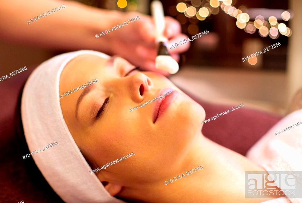 Stock Photo: beautician applying facial mask to woman at spa.