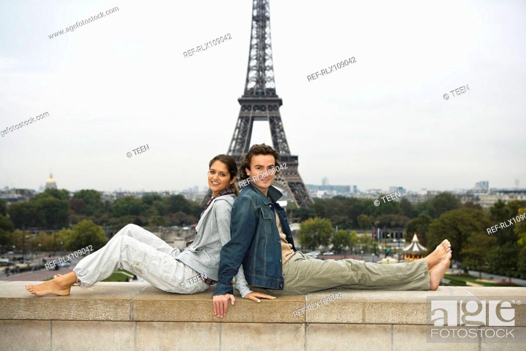 Stock Photo: Young couple lying back to back on wall, Eiffel tower in background.