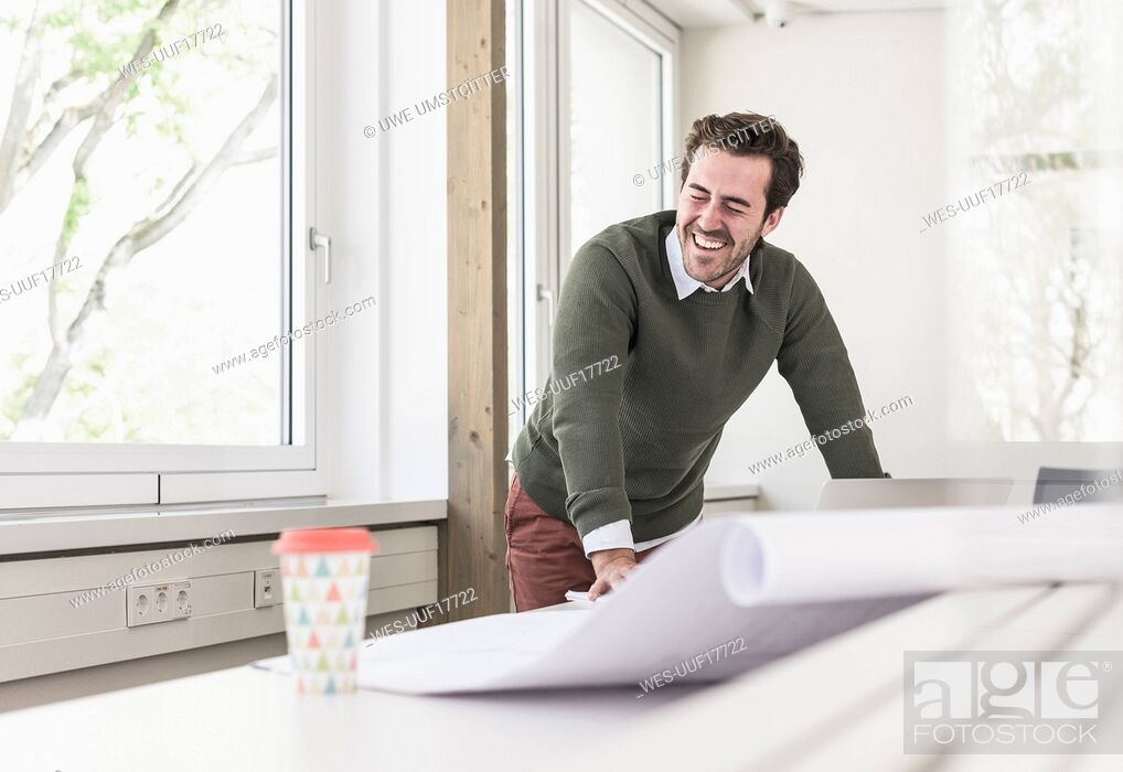 Stock Photo: Laughing young architect working on blueprint in bright office.
