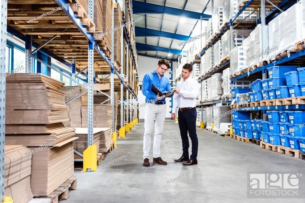Stock Photo: Two businessmen having a meeting in company warehouse.