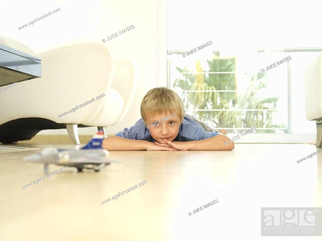 Stock Photo: Blonde boy 5-7 playing with toy plane at home, lying on wooden floor, front view, surface level.